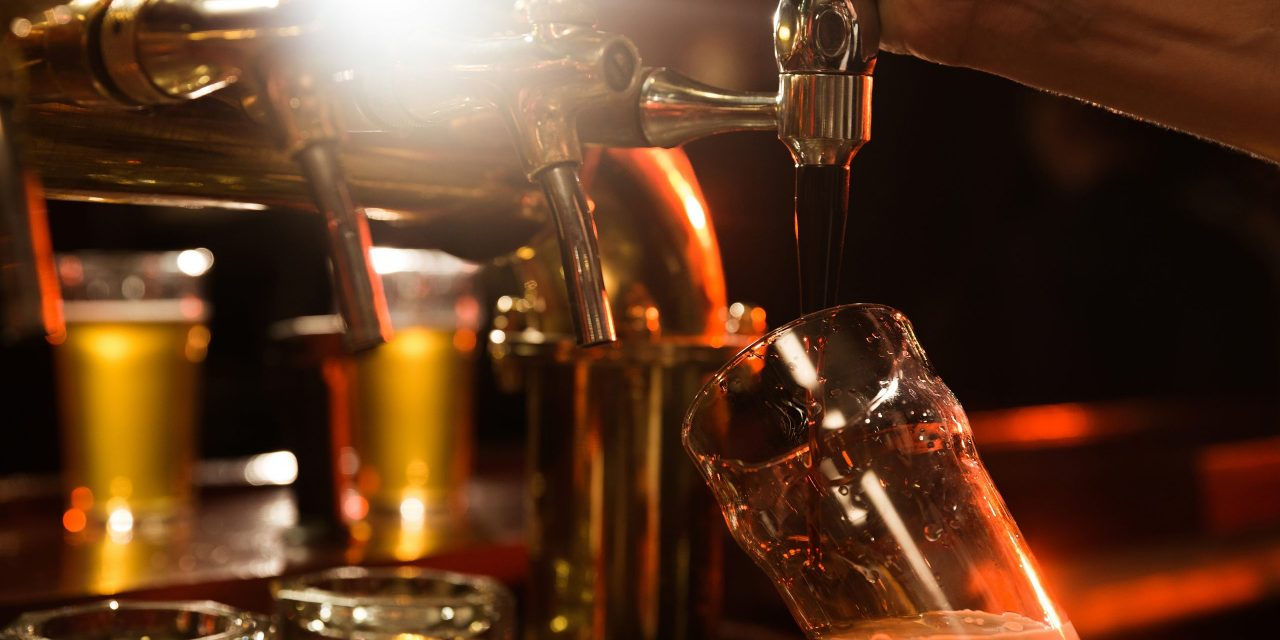 Close up of a bartender pouring beer while standing at the bar counter